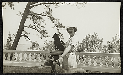 Katharine Ward Lane Weems posed with a dog on a pedestal and holding another dog by the collar
