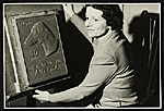 Katharine Lane Weems posing with the plaque she designed for the Dachshund Club of Americas fiftieth anniversary