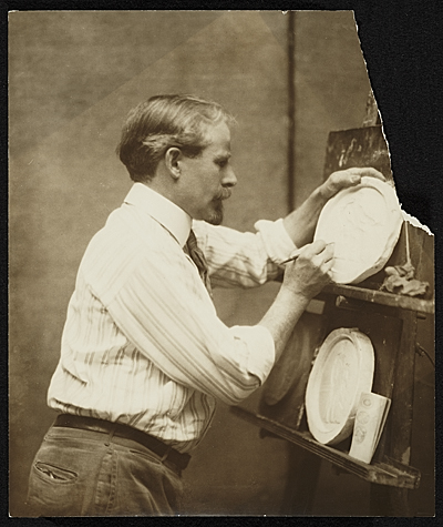 [Adolph Weinman working on a relief]