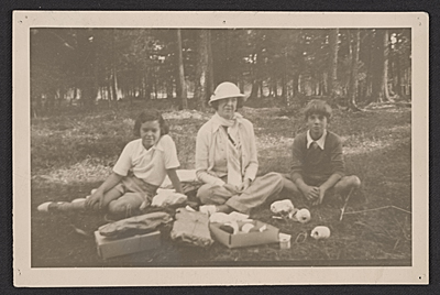 Gloria Vanderbilt, Gertrude Vanderbilt Whitney, and Harry Payne Whitney seated in a grove of trees