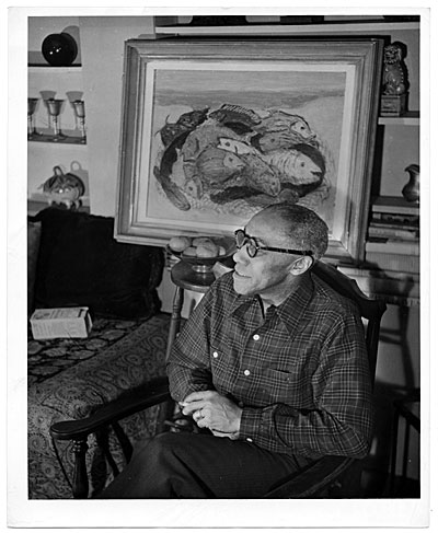 [Ellis Wilson seated in front of painting of fish]