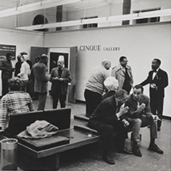 Black and white photograph, taken during the summer of 1969, shows attendees at an Cinque Gallery exhibit opening, including cofounders Norman Lewis (standing in a black suite at far right) and Romare Bearden  (farther left, talking to an unidentified man).