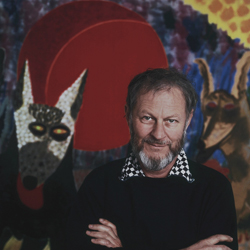Photo is a portrait of Roy De Forest with his arms crossed in front of one of his paintings of two dogs
