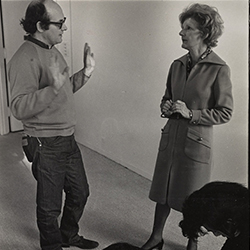 Black and white photograph of Elayne Varian speaking to Sol Le Witt during public installation of artwork at Art in Process V exhibition at Finch College Museum of Art.