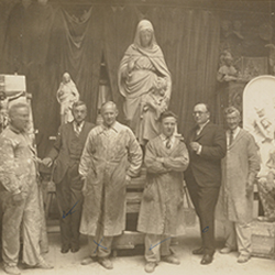 Photograph depicts artists including Fritz Hoffman and Joseph Gerlach with Joseph Sibbel at Joseph Sibbel Studio. The group stands in front of sculptures