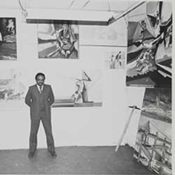 Black and white photograph of Norman Parish standing in gallery space with paintings on the wall