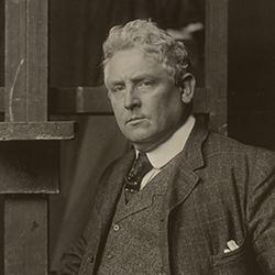Photo is a portrait of Julian Alden Weir standing against an easel in his studio