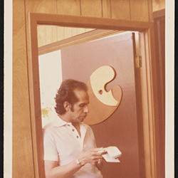 Color photograph of Mel Casas standing in a doorway looking at papers, circa 1977