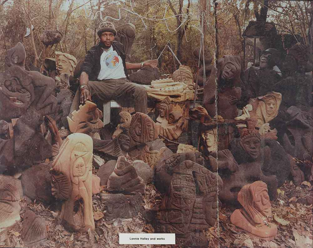 Photograph of Lonnie Holley with sculptures
