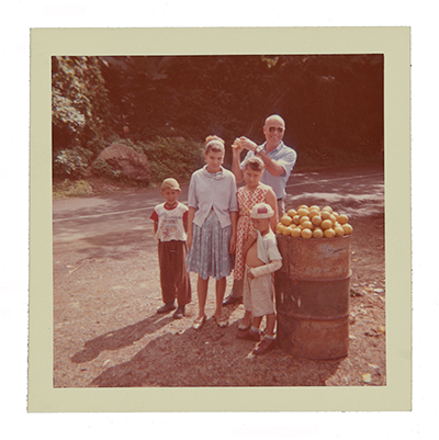 Color photograph of Emilio Sanchez posing with children in Puerto Rico next to a barrel of fruit.