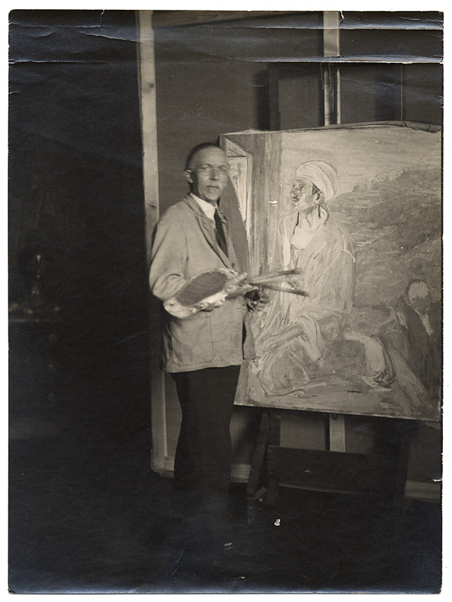 Artist Henry O. Tanner in his studio next to an easel with a painting of Judas