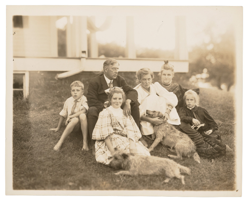 Edmund C. Tarbell and his family photographed in front of their New Hampshire home with their dogs.
