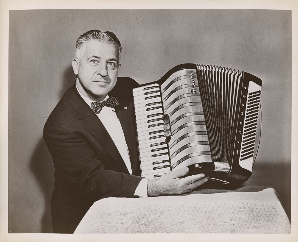 John Vassos holding the Marchesa accordion he designed for the Hohner company.