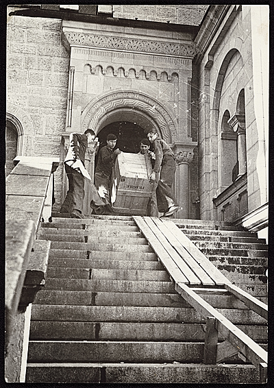 Four men carrying a crate of recovered artworks, previously looted by the  Nazis during World War II, down a staircase at Neuschwanstein Castle, 1945.  James J. Rorimer papers, Archives of American Art, Smithsonian Institution