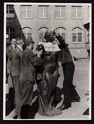 Six men prepare an Aristide Maillol sculpture looted during World War II for transport to France. Sculpture is labeled with sign: Wiesbaden, no. 31. Verso, handwritten: Restitution shipment to France. May 24, 1946. Unidentified photographer. James J. Rorimer papers, Archives of American Art, Smithsonian Institution.