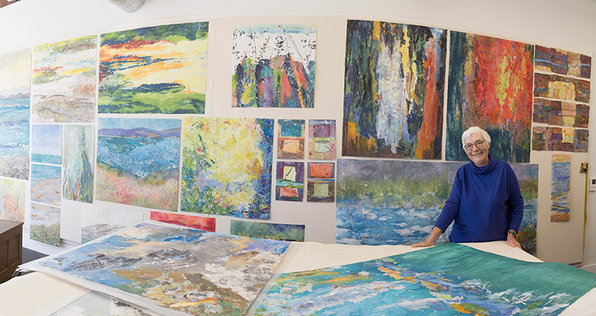 Woman with white hair wearing a blue sweater and glasses in her art studio.