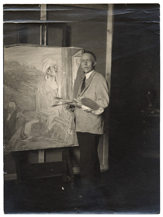 Reverse image of artist Henry O. Tanner in his studio next to an easel with a painting of Judas