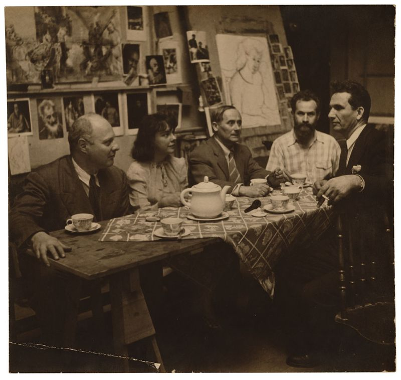 Photograph of Carl Holty and Joan Miró with others at a tea party in an artists studio