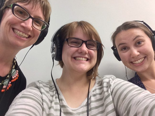 Interns wearing headphones and smiling
