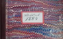 Detail of a stock book dated 1884 with a maroon leather spine and blue, maroon, and beige marbled board with a white sticker.
