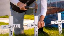 White crosses with names written in black being nailed into the grass by a kneeling woman, who is front of a church.