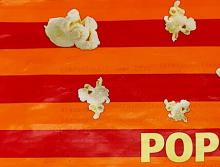 Detail of an orange and bright pink popcorn bag with pictures of popcorn and yellow text that reads pop.