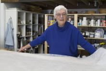 Woman with short white hair wearing a blue sweater and glasses working in an art studio.