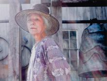 Gray-haired woman in straw hat and lavender dress next to a large bell.